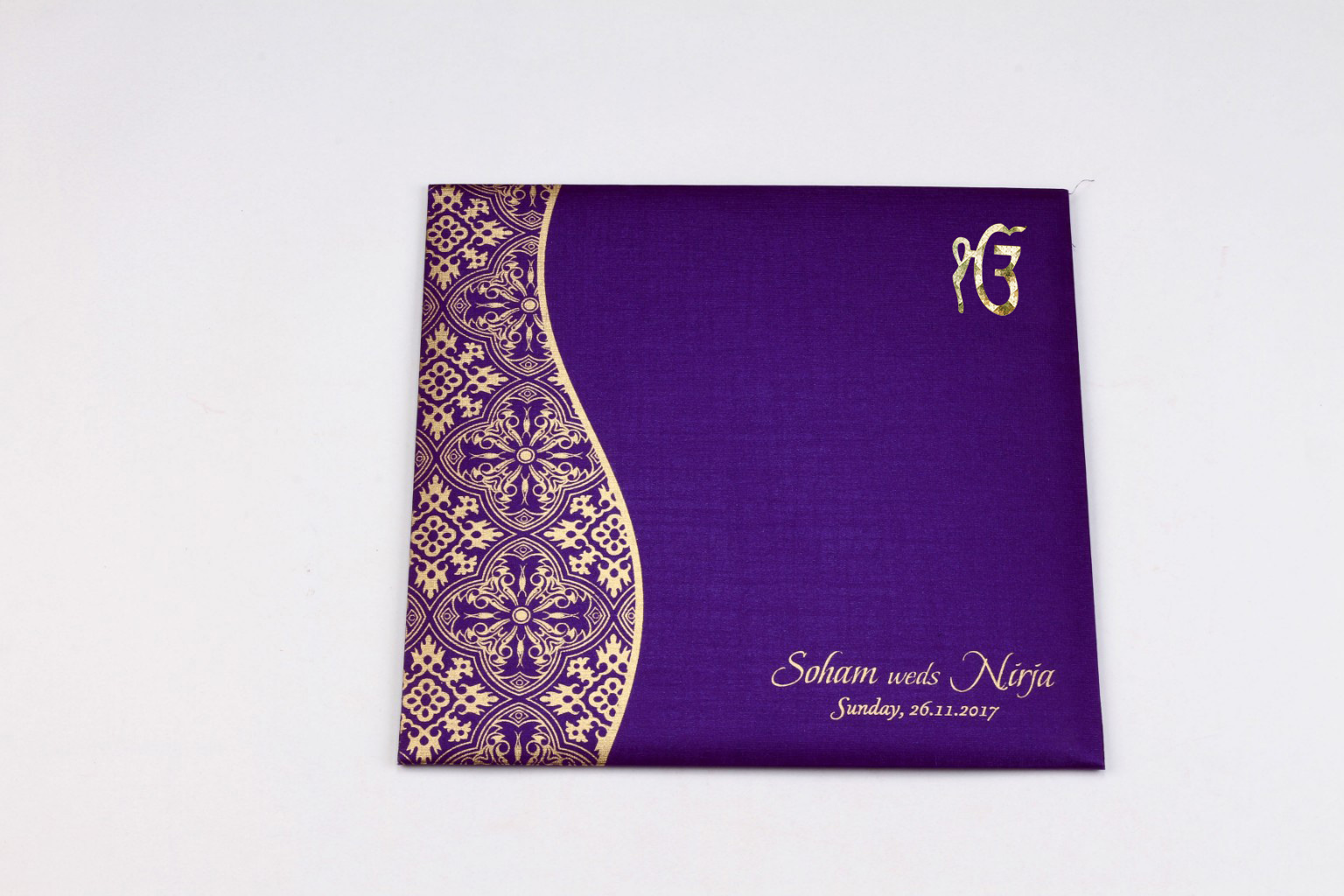 Sikh wedding invite in purple with golden paisley