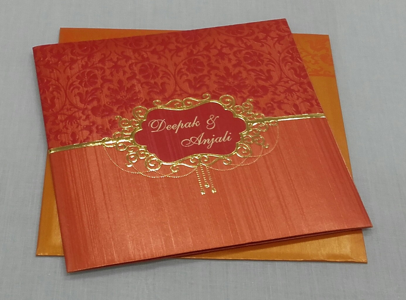 Multifaith indian wedding invitation in rustic orange colour
