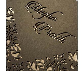 Laser cut floral motifs on a brown cardboard Invitation