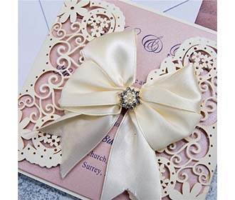 Laser cut wedding invitation in cream with ribbon bow and embellishments