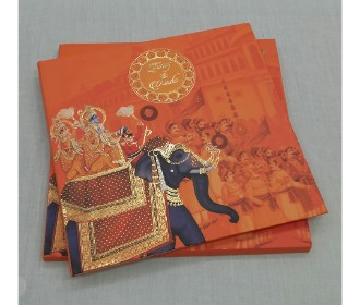 Rajwada look invite with golden and orange touch