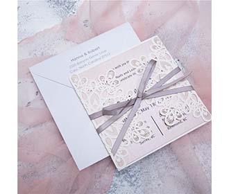 White laser cut wedding invitation with grey ribbon